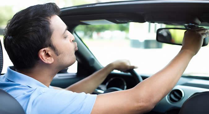 narcissist guy looking in car mirror
